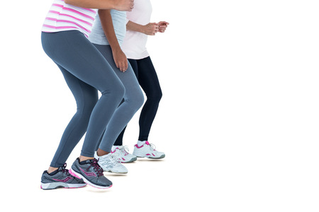 low section: Low section of female friends jogging against white background