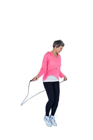 saltar la cuerda: Mujer madura ejercicio con saltar la cuerda contra el fondo blanco Foto de archivo