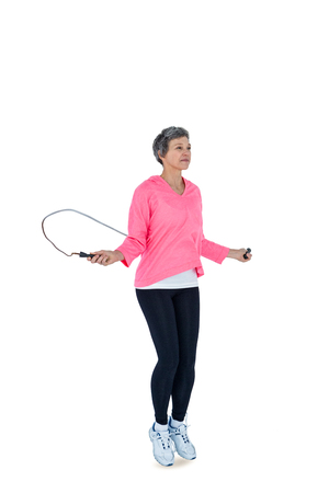 jump rope: Full length of mature woman exercising with jump rope against white background Stock Photo