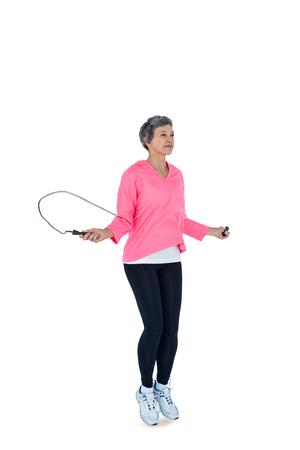 saltar la cuerda: Integral de la mujer madura ejercicio con saltar la cuerda contra el fondo blanco Foto de archivo