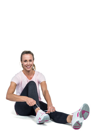 fair woman: Portrait of woman smiling while tying shoelace over white background