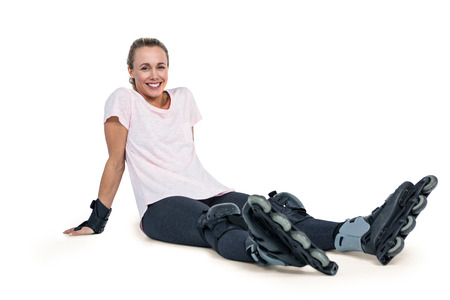 inline skater: Portrait of happy female inline skater relaxing over white background