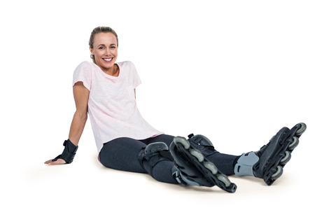 inline skater: Portrait of happy female inline skater relaxing over white background