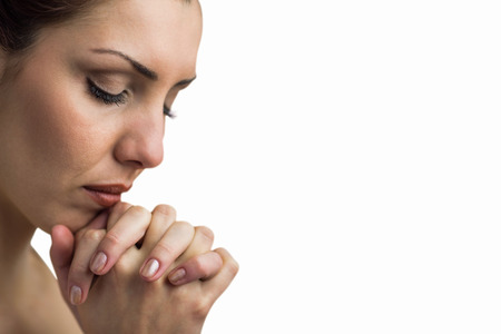 brethren: Close-up of woman praying with eyes closed against white background Stock Photo