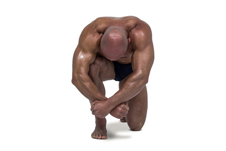muscular body: Muscular man bending on knee against white background Stock Photo