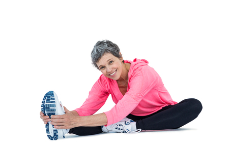 touching toes: Portrait of mature woman exercising over white background Stock Photo