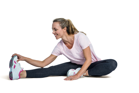 toes: Happy woman touching toes while exercising over white background Stock Photo