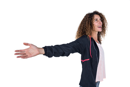 outstretched: Happy young woman with arms outstretched against white backgropund