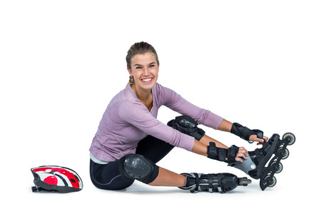 inline: Portrait of happy woman wearing inline skates while sitting over white background