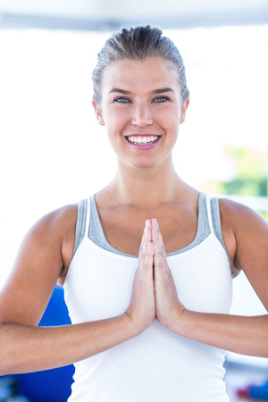 joined: Portrait of a happy woman with hands joined in fitness studio Stock Photo