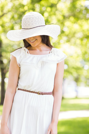 sun hat: Happy young woman in sun hat standing on grassland in park