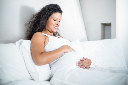 attractive pregnant: Happy attractive pregnant woman resting in bed at home Stock Photo
