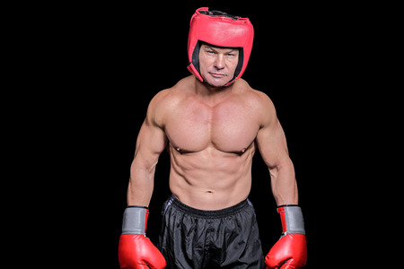 headgear: Portrait of shirtless man with boxing headgear and gloves against black background Stock Photo