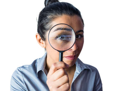 closer: Woman examining with a magnifying glass against a white background Stock Photo