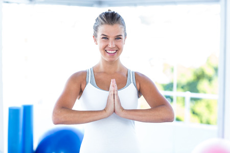 joined: Portrait of a smiling woman with hands joined in fitness studio
