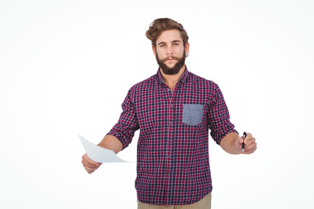 pen: Portrait of confident hipster holding pen and paper standing against white backgroiund