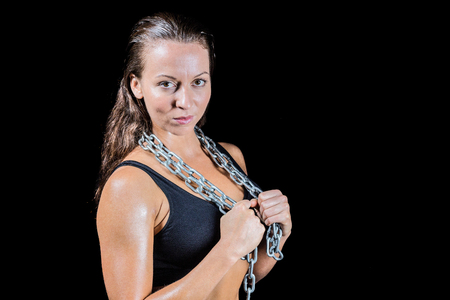 female fighter: Portrait of female fighter with chain against black background