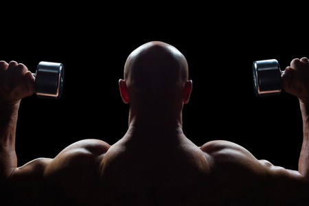 shaved head: Rear view of man exercising with dumbbells against black background