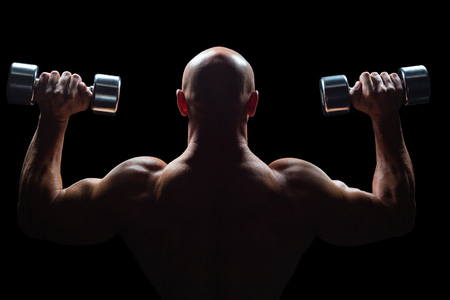 shaved head: Rear view of muscular man lifting dumbbells against black background