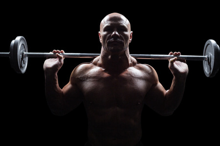 shaved head: Portrait of bald man lifting crossfit against black background
