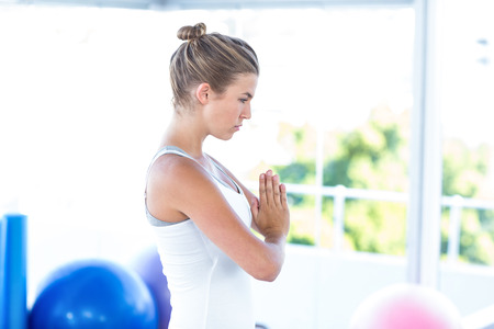 joined: Side view of woman with hands joined in fitness studio Stock Photo