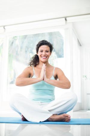 manos unidas: Retrato de cuerpo entero de la mujer embarazada sonriente sentado en la estera del ejercicio con las manos juntas en el hogar