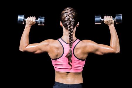 trenzas en el cabello: Vista trasera de la mujer del pelo trenzado ejercicio de pesas contra el fondo negro