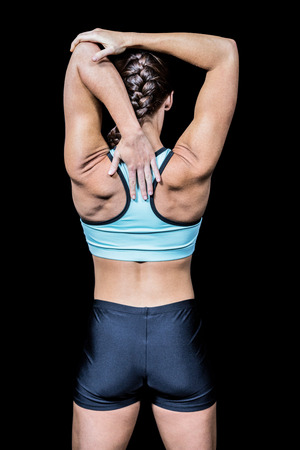 braided flexible: Rear view of woman stretching hands against black background