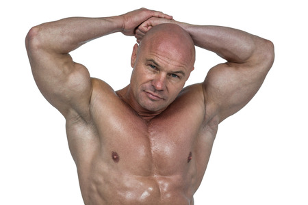 shaved head: Portrait of bodybuilder with hands behind head against white background