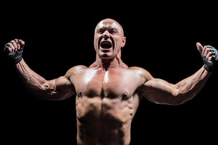 outstretched: Angry fighter with arms outstretched against black background