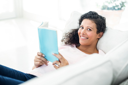 embarazada feliz: Retrato de la mujer embarazada sonriendo mientras lee el libro en el sofá en casa