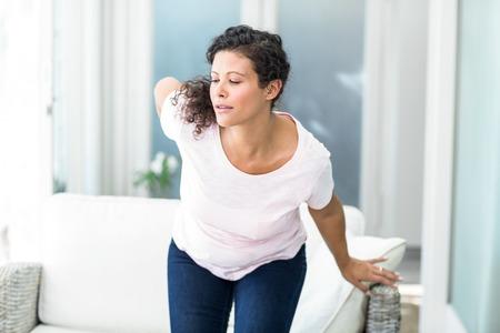 levantandose: Mujer embarazada levantarse de sof� con mano en la cadera en el hogar Foto de archivo