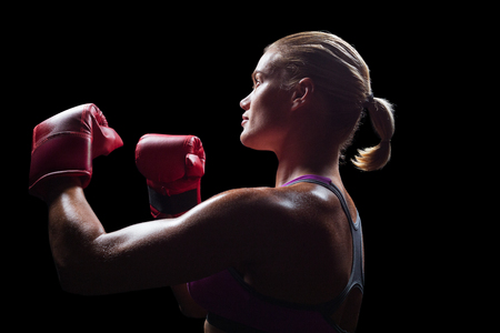 fighting stance: Side view of female boxer with fighting stance against black background