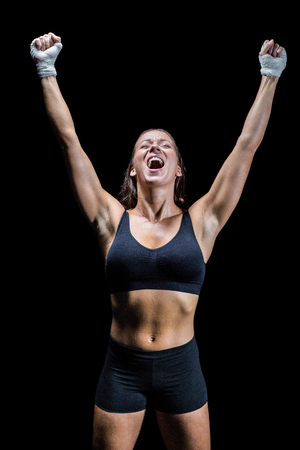 Cheerful winning athlete with arms raised against black background Stock Photo