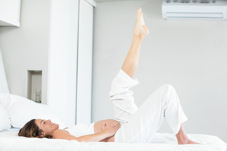 lying on stomach: Happy pregnant woman with leg up while lying on bed