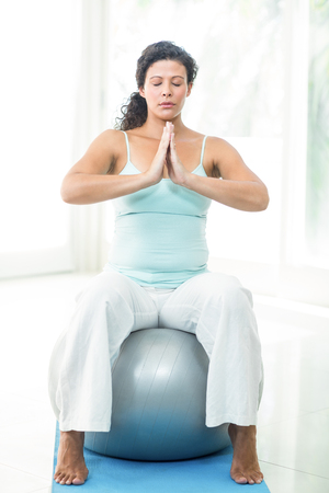 joined hands: Full length of pregnant woman with joined hands and eyes closed on exercise balls in gym