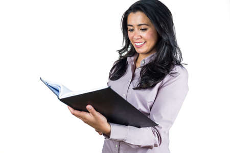 ledger: Businesswoman looking at a business ledger against a white background