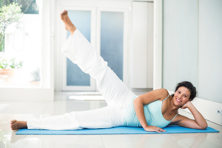home keeping: Full length portrait of smiling pregnant woman keeping in shape at home