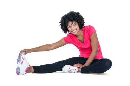 Portret van een jonge vrouw aan te raken tenen tijdens het sporten tegen een witte achtergrond