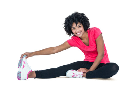 Portrait of young woman touching toes while exercising against white background