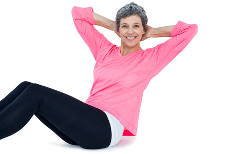 ups: Portrait of mature woman doing sit ups over white background Stock Photo