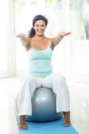 expectant arms: Full length portrait of smiling pregnant woman exercising with ball in fitness studio Stock Photo
