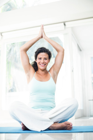 joined hands: Full length portrait of happy pregnant woman sitting on exercise mat with joined hands at home Stock Photo
