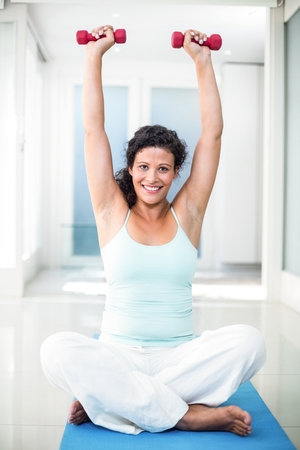 expectant arms: Full length of pregnant woman lifting dumbbells while sitting on exercise mat in fitness studio Stock Photo