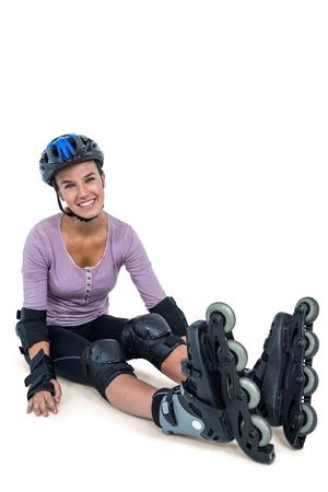 inline skater: Portrait of happy female inline skater resting over white background