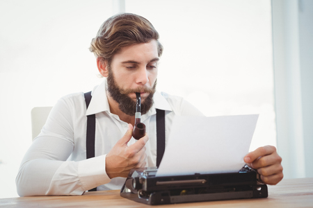 smoking pipe: Hipster with smoking pipe working on typewriter at desk in office Stock Photo