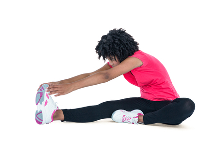 toes: Young woman touching toes while exercising against white background