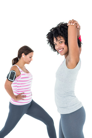 portable mp3 player: Happy woman exercising while female friend stretching against white background