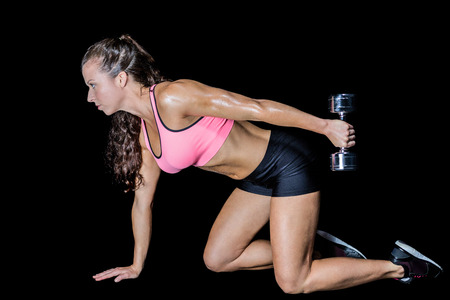 woman kneeling: Side view of woman kneeling while lifting dumbbell against black background Stock Photo
