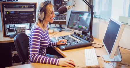 Side view of female radio host broadcasting through microphone in studio